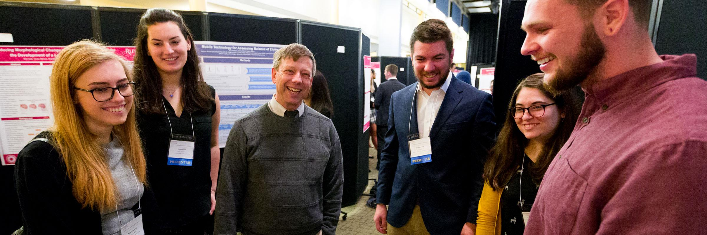 Presenters, guests, and Aresty Director Vadim Levin discussing poster presentations at the Annual 2018 Symposium.
